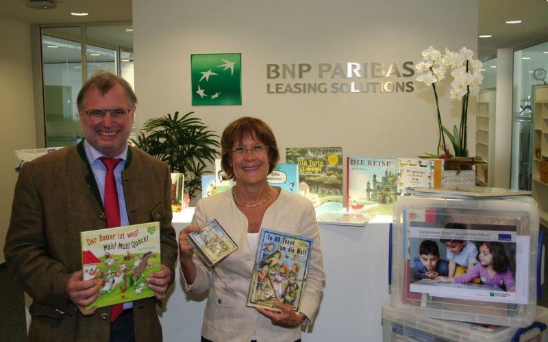 Rudolf Bünten von der BNP Paribas Leasing Solutions in Köln übergibt die Bücherboxen an Barbara Zaabe