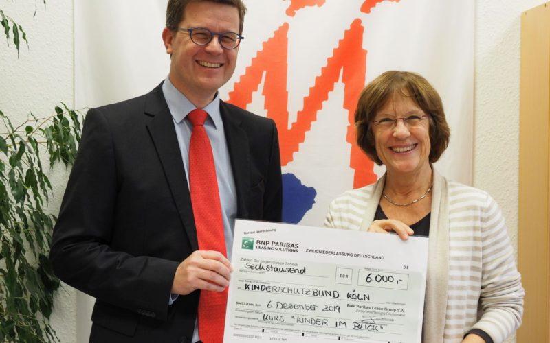 Eric Gandemer überreicht den Spendenscheck an Geschäfsführerin Barbara Zaabe