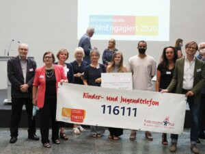 Die Delegation des Kinderschutzbundes nach der Preisverleihung mit Bürgermeisterin Elfi Scho-Antwerpes und Ehrenamtspatin Maite Kelly im Hintergrund